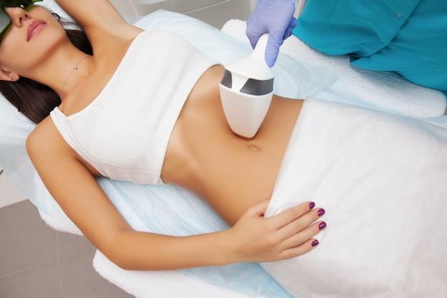 Laserepilation und kosmetologie im schönheitssalon. verfahren zur haarentfernung. konzept für laser-epilation, kosmetologie, spa und haarentfernung. schöne frau, die das haar entfernt auf bauch erhält