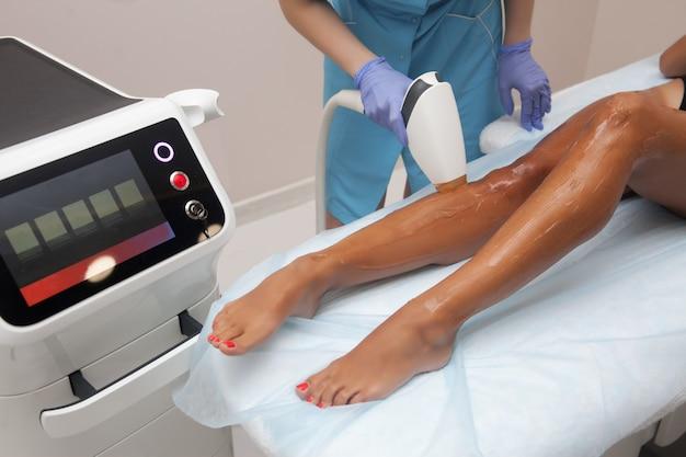 Laserepilation und kosmetologie im schönheitssalon. verfahren zur haarentfernung. konzept für laser-epilation, kosmetologie, spa und haarentfernung. schöne frau, die das haar entfernt auf fahrwerkbeinen erhält