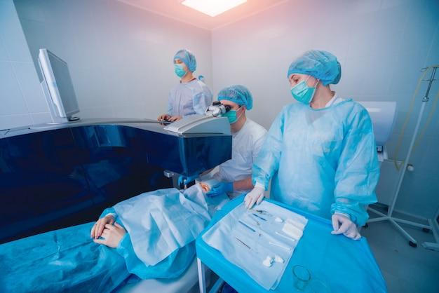 Lasersichtkorrektur. ein patient und ein team von chirurgen im operationssaal während der augenchirurgie. augenlidspekulum. lasik-behandlung.