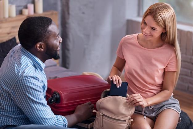 Lass die flitterwochen beginnen. freudige junge internationale paarverpackung, bevor sie zur reise geht und im schlafzimmer lächelt.