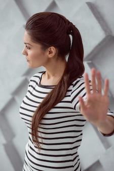 Lass mich alleine. nette angenehme junge frau, die ihre hand zeigt und ihren kopf dreht, während sie allein sein will