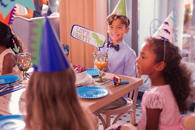 Lass uns party machen. fröhlicher entspannter junge, der partyhut trägt und zeichen hält, lässt party mit grünem dinosaurier