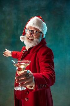 Lass uns party machen. moderner stilvoller weihnachtsmann in rotem modischem anzug und cowboyhut auf dunklem hintergrund. sieht aus wie ein rockstar. silvester und heiligabend, feiern, feiertage, winterstimmung, mode.
