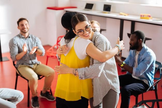 Lass uns umarmen. fröhliche, freundliche junge frauen, die sich gut fühlen und sich umarmen, während sie während der psychologischen sitzung mitten im kreis stehen