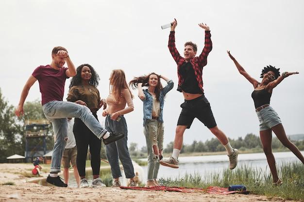 Lass uns verrücktes tun. eine gruppe von menschen hat ein picknick am strand. freunde haben spaß am wochenende.