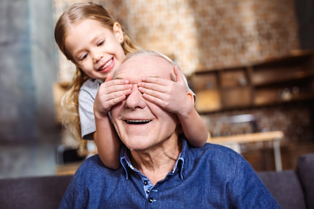 Lass uns was spielen. nettes kleines lächelndes mädchen, das augen ihres großvaters schließt, während spaß hat
