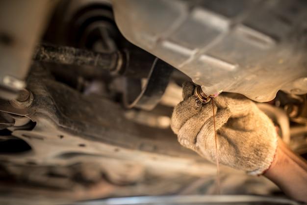 Lassen sie das alte öl durch die ablassschraube aus dem motor ab. ölwechsel in einem automotor.