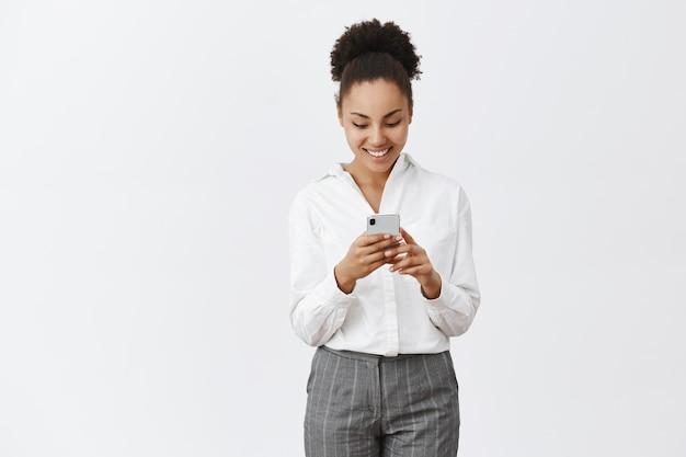 Lassen sie mich nachrichten überprüfen. charmante freundliche und glückliche afroamerikanische frau in weißem hemd und in der hose, hält smartphone, blickt unterhalten und amüsiert auf gerätebildschirm während des spielens des telefonspiels
