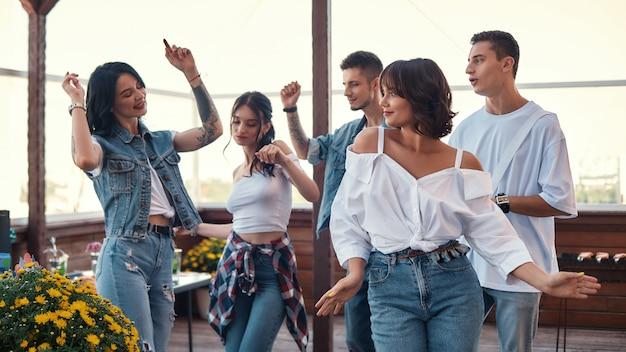 Lassen sie uns eine gruppe glücklicher freunde tanzen, die eine party auf der dachterrasse genießen?