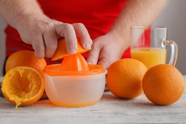 Lassen sie uns orangensaft mit einem quetscher machen