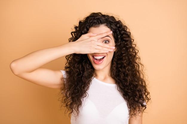 Lasst uns ein spiel spielen! foto der hübschen lustigen dame, die auge halb spielerischen gesichtsausdruckfinger versteckt, tragen weiße freizeitkleidung lokal beigen pastellfarbenen hintergrund