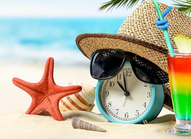 Last-minute-angebote. sommerferienkonzept. zeit zum entspannen. wecker mit strohhut, seestern, regenbogencocktail am sandstrand und meereshintergrund.