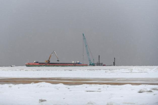 Lastkahn mit kran. bagger, der auf see arbeitet. starker nebel im arktischen meer. bau marine offshore-arbeiten. dammbau, kran, lastkahn, bagger.