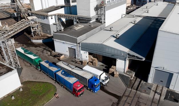Lastwagen, die darauf warten, in der draufsicht einer holzbearbeitungsfabrik beladen zu werden