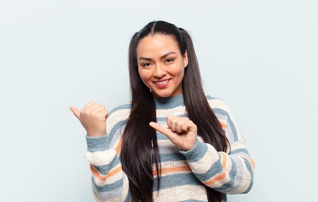 Lateinamerikanische frau, die fröhlich lächelt und beiläufig zeigt, um platz auf der seite zu kopieren, sich glücklich und zufrieden fühlend