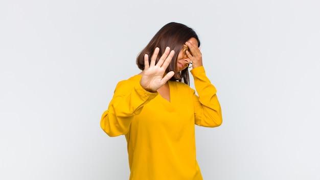 Lateinamerikanische frau, die gesicht mit hand bedeckt und andere hand nach vorne legt, um kamera zu stoppen, fotos oder bilder ablehnend