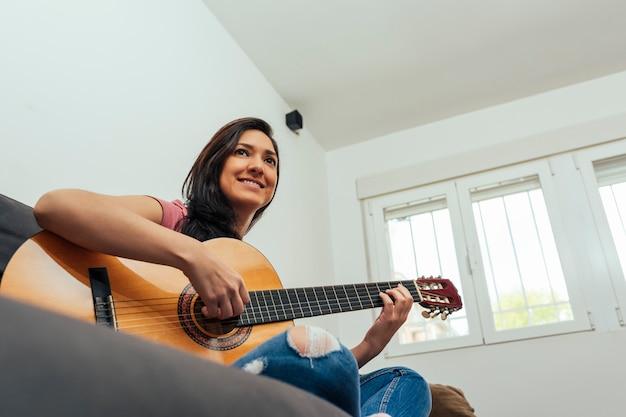 Lateinamerikanische frau, die gitarre im wohnzimmer sitzt, sitzt auf der couch