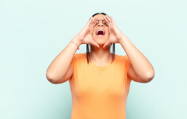 Lateinamerikanische frau, die sich glücklich, aufgeregt und positiv fühlt, mit den händen neben dem mund einen großen schrei ausstößt und ruft