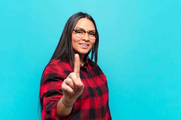 Lateinamerikanische frau, die stolz und selbstbewusst lächelt und die nummer eins triumphierend posiert und sich wie eine anführerin fühlt