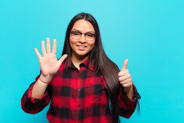 Lateinamerikanische frau lächelt und sieht freundlich aus, zeigt nummer sechs oder sechste mit der hand nach vorne und zählt herunter