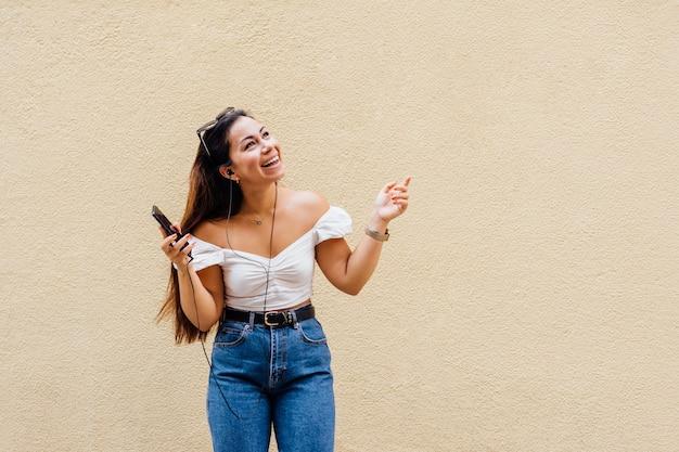 Lateinamerikanische frau macht ein selfie mit ihrem smartphone, während sie musik hört