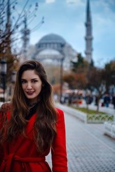 Lateinamerikanische frau oder türkische frau in einem roten stilvollen mantel vor der berühmten blauen moschee in istanbul