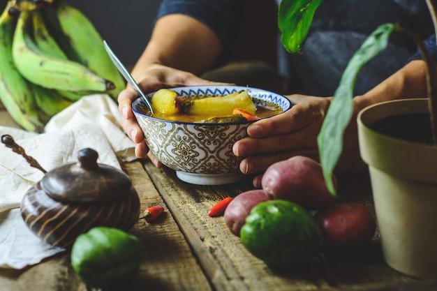 Lateinamerikanische gemüsesuppe, hände, die den teller greifen. zutaten karotte, chayote, süßkartoffel, grüner bananenpfeffer.
