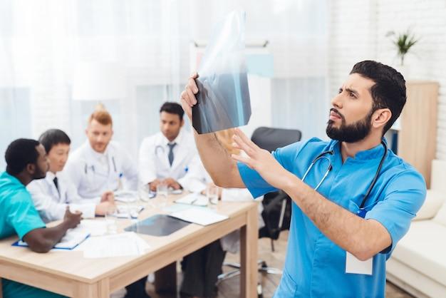 Lateinamerikanischer arzt mit beckenbefund des röntgenpatienten.