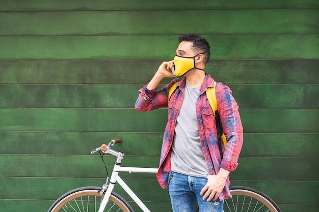 Lateinamerikanischer junger mann, der maske trägt und telefon im freien verwendet.