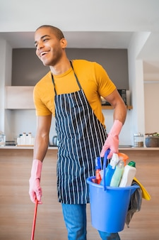 Lateinamerikanischer mann, der einen eimer mit reinigungsgegenständen hält