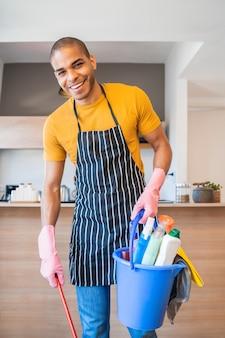 Lateinamerikanischer mann, der einen eimer mit reinigungsgegenständen hält.