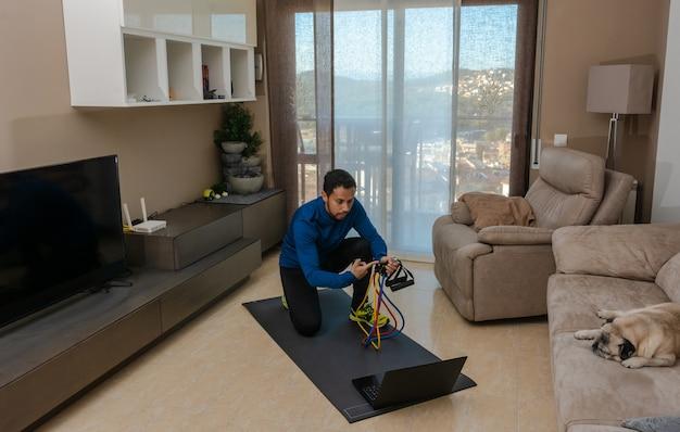 Lateinamerikanischer mann, der in seinem wohnzimmer mit einem gummiband trainiert, während er an einem online-kurs teilnimmt