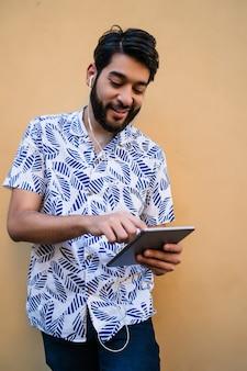 Lateinamerikanischer mann, der sein digitales tablett mit kopfhörern benutzt.