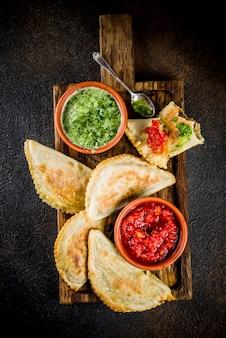 Lateinamerikanisches, mexikanisches, chilenisches essen. traditionelle empanadas aus gebackenem gebäck mit rindfleisch, zwei scharfen soßen