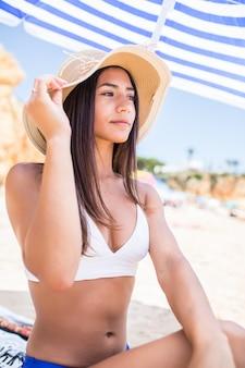 Lateinische frau der jungen schönheit im bikini und im strohhut, die unter sonnenschirm am strand nahe der seeküste sitzen.