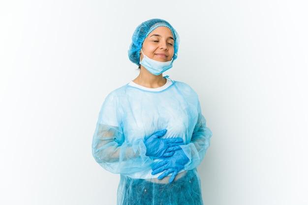 Lateinische frau des jungen chirurgen berührt bauch, lächelt sanft, ess- und zufriedenheitskonzept.