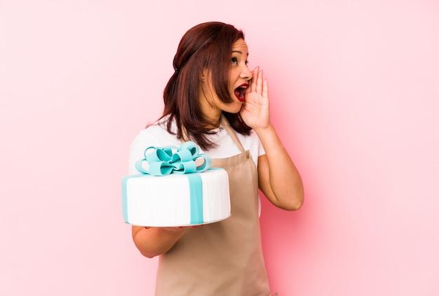 Lateinische frau des mittelalters, die einen kuchen lokalisiert auf einer rosa wand schreit und hält palme nahe geöffnetem mund hält.
