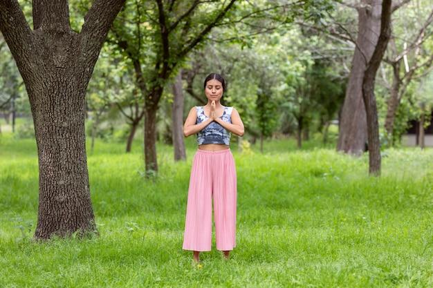 Lateinische frau, die an der seite eines baumes im park auf grünem gras mit einem rosa outfit meditiert