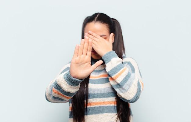 Lateinische frau, die gesicht mit hand bedeckt und andere hand vorne legt, um kamera zu stoppen, fotos oder bilder ablehnend