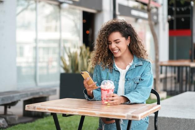 Lateinische frau, die ihr handy benutzt, während sie ein kaltes getränk in einem café draußen auf der straße trinkt. urbanes konzept.
