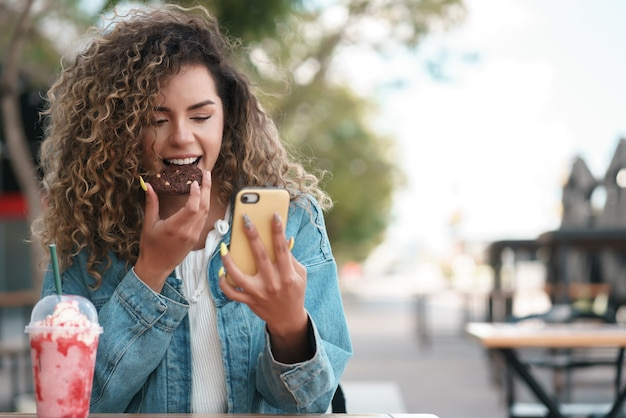 Lateinische frau, die ihr handy benutzt, während sie einen keks isst und ein kaltes getränk in einem café trinkt. urbanes konzept.