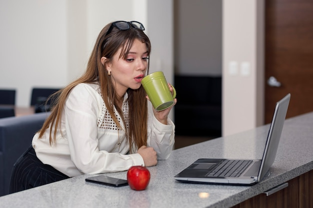 Lateinische frau, die kaffee trinkt, während sie an ihrem computerkonzept arbeitet, zu hause zu sein