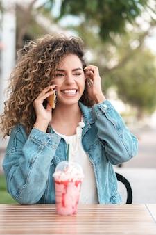 Lateinische frau, die telefoniert, während sie ein kaltes getränk in einem café trinkt. urbanes konzept.