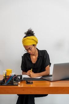 Lateinische frau, die zu hause büro mit laptop und dokumenten arbeitet