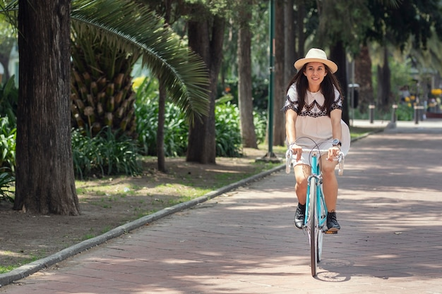 Lateinische frau in weißem kleid und hut, die mit dem fahrrad im park spazieren geht
