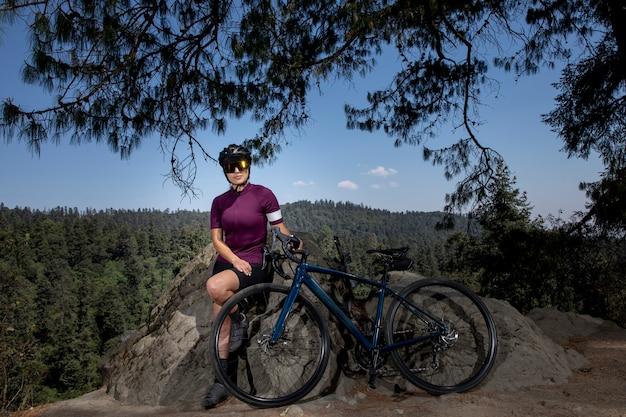 Lateinische frau mit fahrrad ruht im wald mit einer landschaft von bäumen im hintergrund