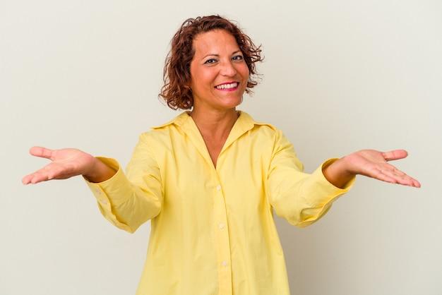 Lateinische frau mittleren alters, die auf weißem hintergrund isoliert ist, macht skala mit armen, fühlt sich glücklich und selbstbewusst.