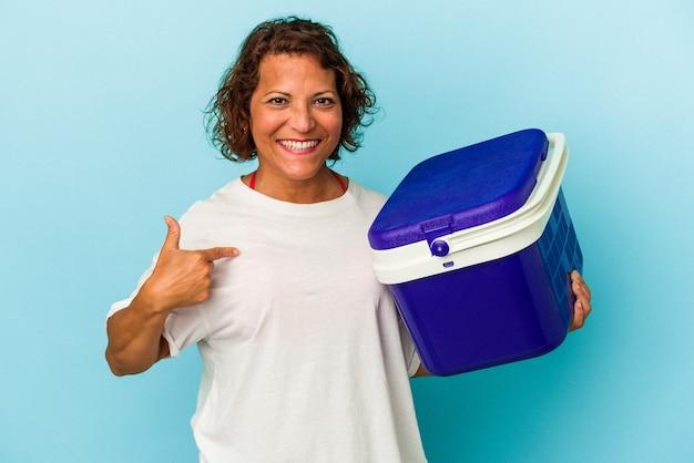 Lateinische frau mittleren alters einzeln auf blauem hintergrund, die mit der hand auf einen hemdkopierraum zeigt, stolz und selbstbewusst