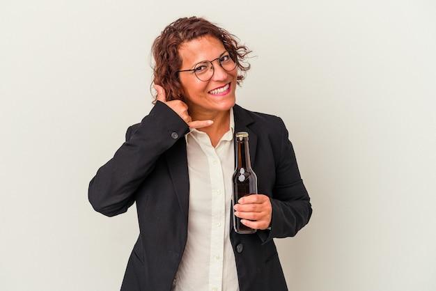 Lateinische geschäftsfrau mittleren alters, die ein bier auf weißem hintergrund hält, das eine handyanrufgeste mit den fingern zeigt.