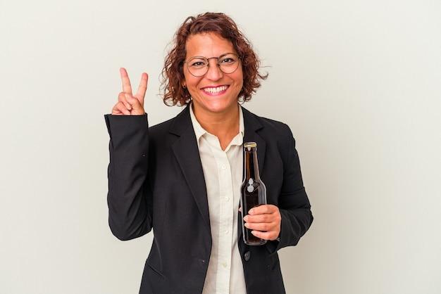 Lateinische geschäftsfrau mittleren alters, die ein bier auf weißem hintergrund hält, das nummer zwei mit den fingern zeigt.
